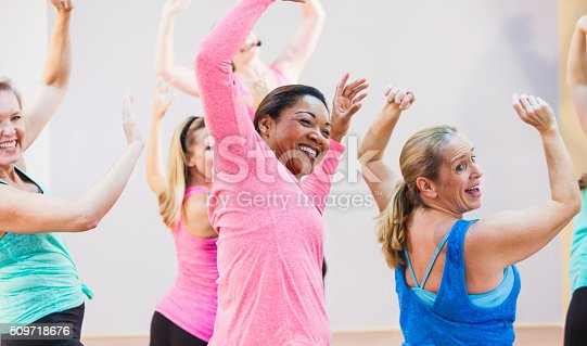 A multi-ethnic group of women having fun taking an exercise class.  The instructor is out of focus in the background, wearing a microphone.  The main focus is on the African American woman in pink and the Caucasian woman in royal blue, arms raised, laughing in the foreground.