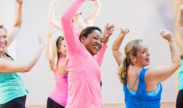 group of multi-ethnic women in exercise class - aerobics stock photos and pictures