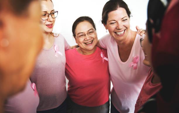 bir grup çok ırklı kadınlar pembe gömlek giymek - breast cancer awareness stok fotoğraflar ve resimler