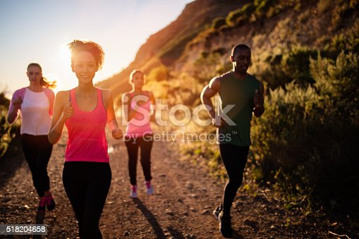 Group of multi-ethnic young adult friends running outdoors with sun flare