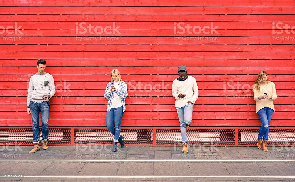 Group of multiracial fashion friends using smartphone outdoors Group of multiracial fashion friends using smartphone with red wood background - Technology addiction in urban lifestyle with disinterest towards each other - Addicted people to modern mobile phones Addict Stock Photo