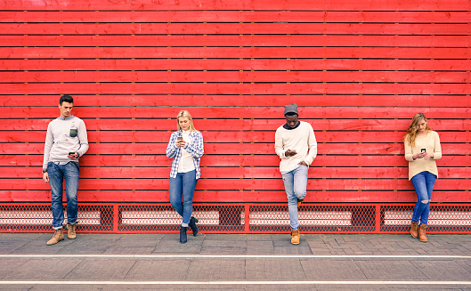 Group Of Multiracial Fashion Friends Using Smartphone Outdoors Stock Photo - Download Image Now