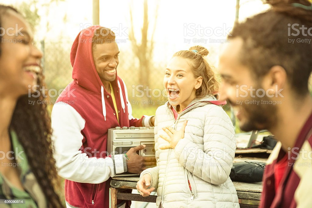Group of multiracial friend couples having fun time with music stock photo