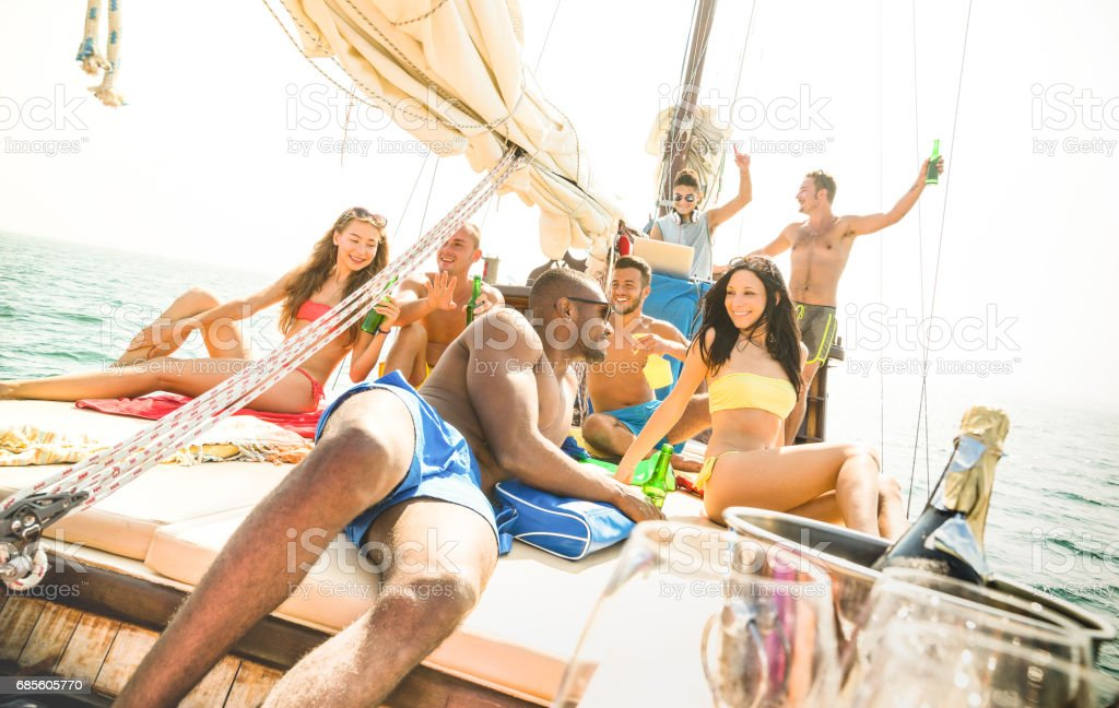 Group of multiracial friends having fun at sail boat party with dj set - Friendship concept with young multi racial people on sailboat - Travel lifestyle on exclusive vibe mood - Warm bright filter royalty-free 스톡 사진