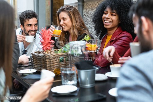 Group of multiracial friends having fun time in a coffee drinking coffee cappuccino and fruit juice