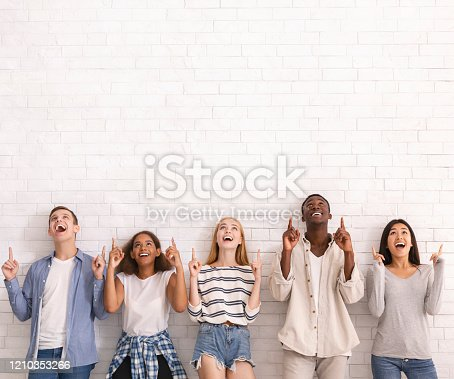 Wow, look at that. Group of multiracial excited friends pointing up at copy space over white brick wall