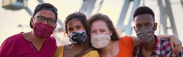 Group of multiracial friends taking photo with face mask on Multiethnic happy face having fun teenagers only stock pictures, royalty-free photos & images