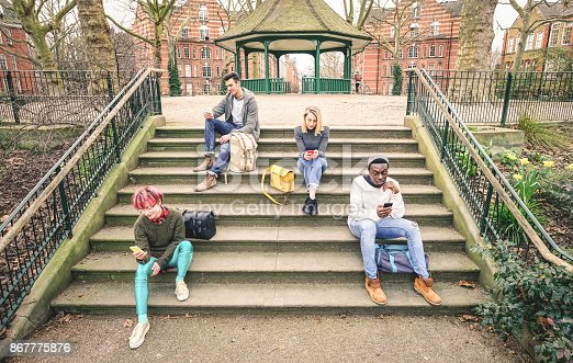 istock Group of multiracial friends using mobile smart phone sitting on stairs at park - Young hipster people addicted by smartphone on social network community - Technology concept - Desaturated color tones 867775876