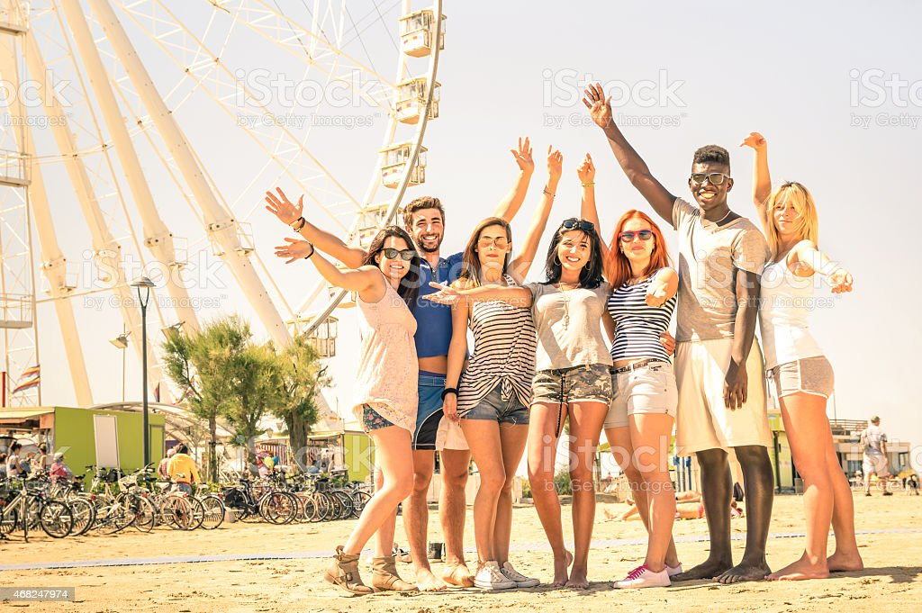 Group of multiracial happy friends cheering at the beach stock photo