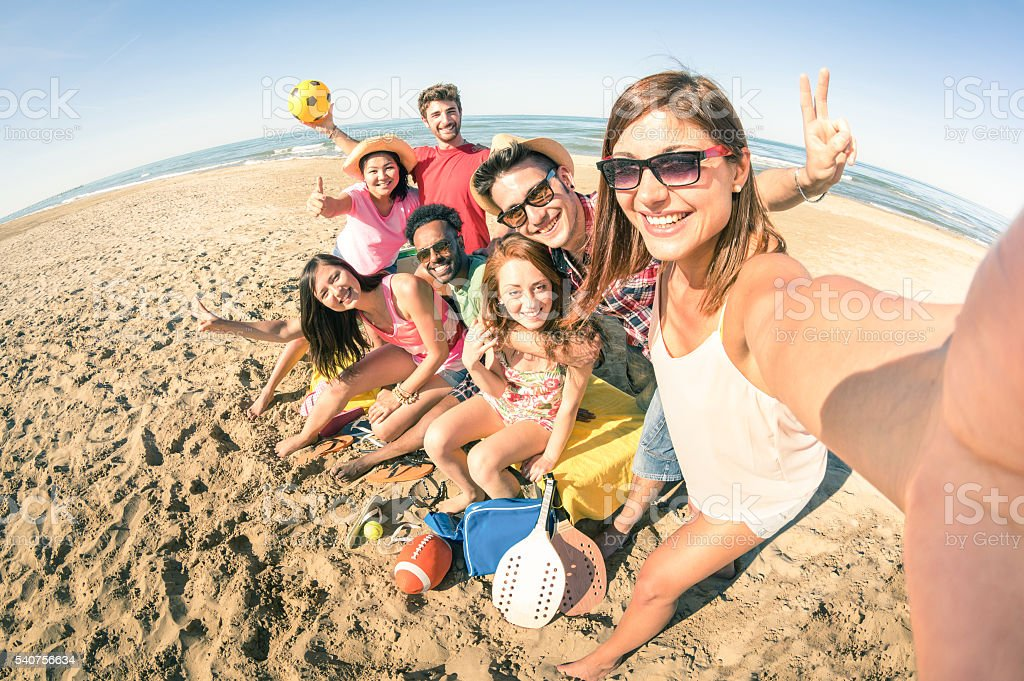 Group of multiracial happy friends taking fun selfie at beach stock photo