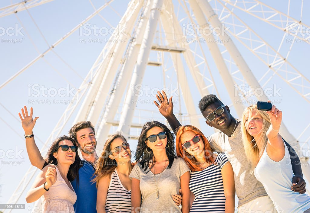 Group of multiracial happy friends taking selfie at ferris wheel stock photo
