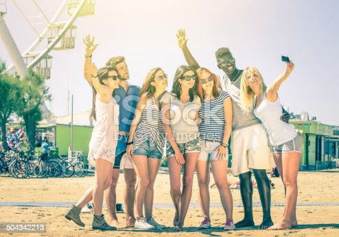 Group of multiracial happy friends taking a selfie at ferris wheel - International concept of happiness and multi ethnic friendship all together against racism for peace and fun - Vintage filtered look
