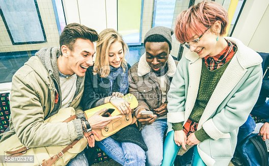 istock Group of multiracial hipster friends having fun in subway train - Urban friendship concept with young people watching mobile phone in city underground area - Vintage filter with focus on blond girl 858702376