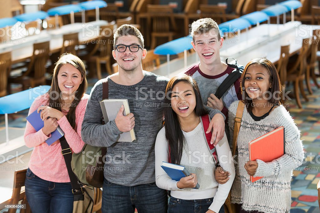 Group of multiracial teenage students in the library stock photo