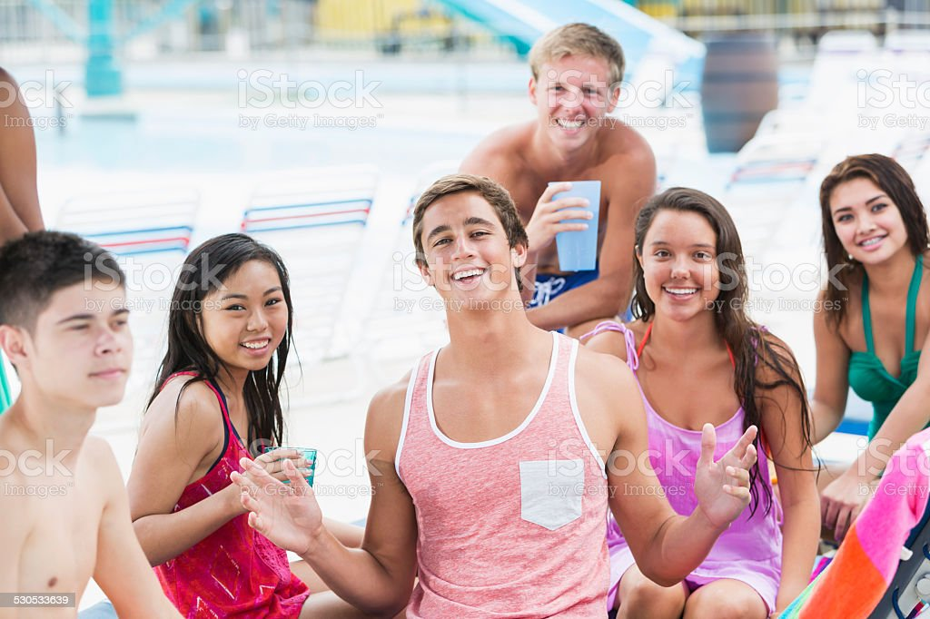Group of multiracial teenagers hanging out on pool deck stock photo