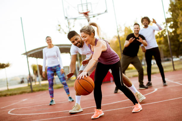 Group of multiracial young people   playing basketball outdoors Group of multiracial young people   playing basketball  on court at outdoors basketball ball stock pictures, royalty-free photos & images