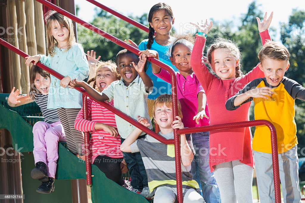 Group of multracial children waving on a playground stock photo