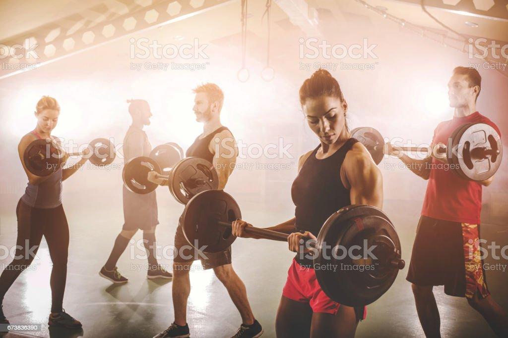 Barbell ile egzersiz kas yapı sporcular grubudur. royalty-free stock photo