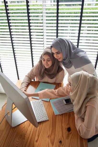Grupo de estudiantes musulmanes usando y aprendiendo con la computadora. - foto de stock