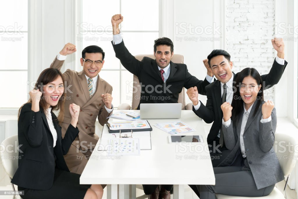 Group of muti ethnicity business people team success achievement with arm raised to celebrating good job in the office. Business people team togetherness happiness Concept. stock photo