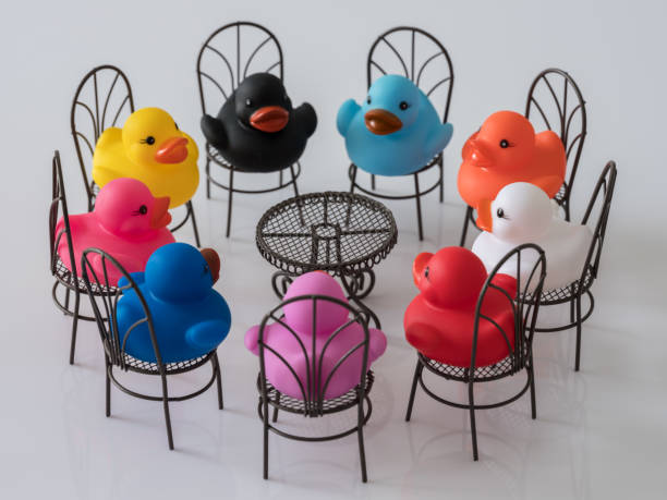group of nine different colored ducks on chairs around a table facing each other, scene set on a white background. - respect stock photos and pictures