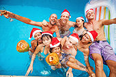 mixed raced  group of nine people celebrating christmas in a swimming pool (focus on frontal row of people)
