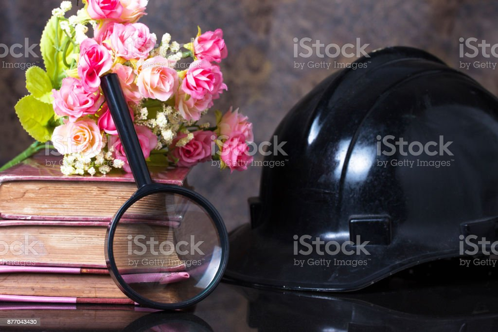 Group of objects on a granite, magnifying glass, old books,artificial flower, black helm ,Still life stock photo