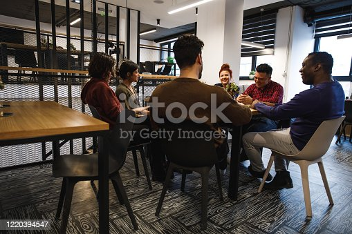 Wide shot of a group of office coworkers sitting at the table in the lounge area and sharing enjoyable time together.