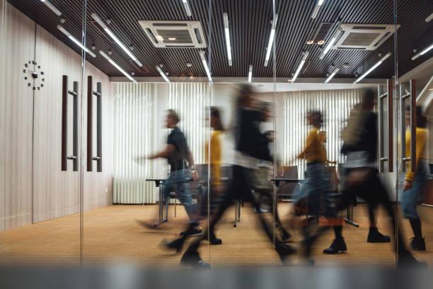 Gruppe von Büromitarbeitern im Coworking Center. Geschäftsleute, die auf modernem Freiraum spazieren gehen. Bewegungsunschärfe. Konzept – Foto