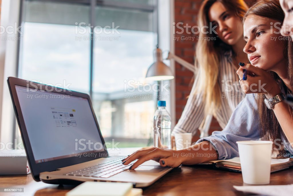 Group of office workers using a laptop together stock photo