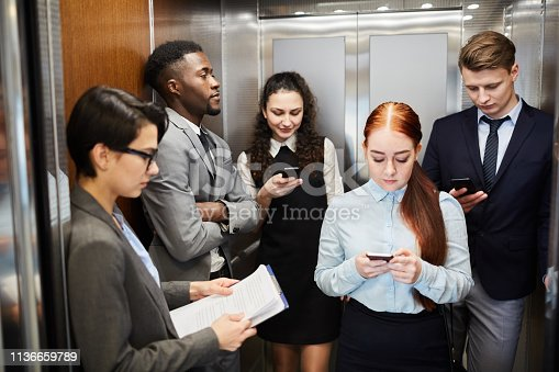 Multiethnic men and women using smartphones while standing in elevator of office
