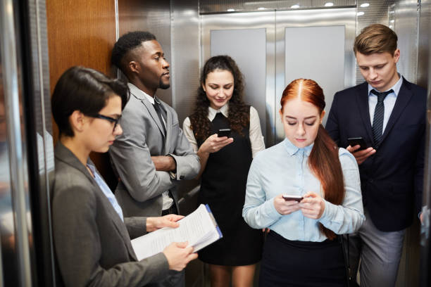 Gruppe von Büroangestellten mit Telefonen im Aufzug – Foto