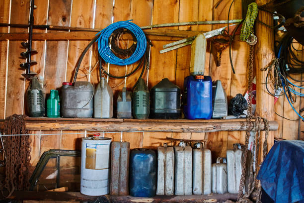 A group of old canisters and cylinders stand on shelves in a wooden shed. stock photo