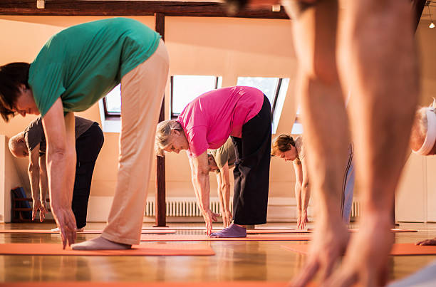 Group of old people stretching to touch the toes. Group of seniors exercising in a health club and trying to touch their toes. touching toes stock pictures, royalty-free photos & images