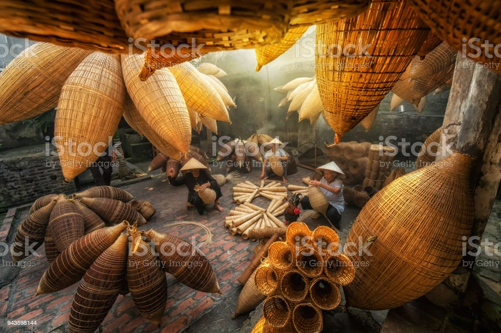 Group of Old Vietnamese female craftsman making the traditional bamboo fish trap or weave at the old traditional house in Thu sy trade village, Hung Yen, Vietnam, traditional artist concept stock photo