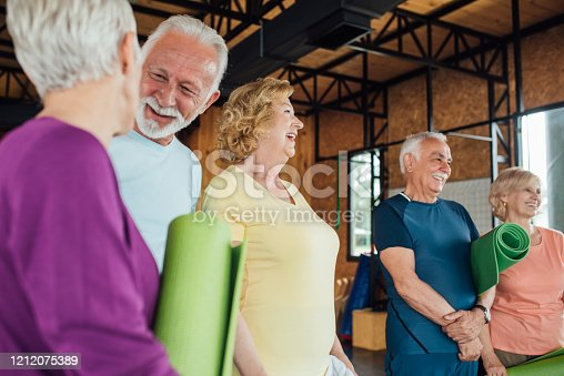 1047537292 istock photo Group of older people gathering for a yoga class 1212075389