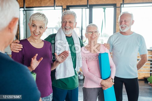 1047537292 istock photo Group of older people having fun and relaxing before exercising yoga together 1212075387