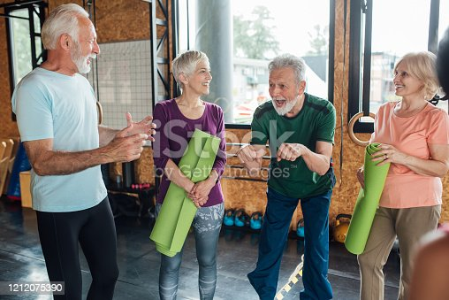 1047537292 istock photo Group of older people having fun before the yoga class 1212075390