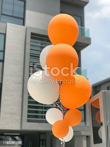 istock Group of orange and white balloons balloons 1163091195