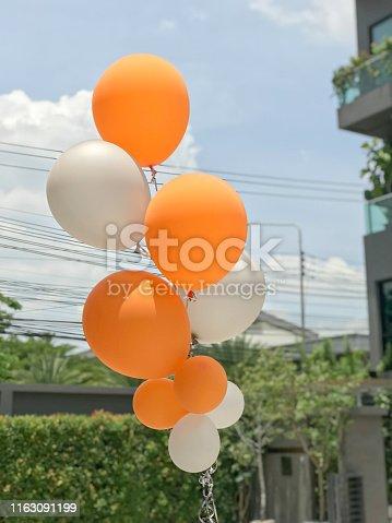 istock Group of orange and white balloons balloons 1163091199