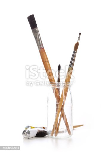 istock Group of paintbrushes in a glass jar and tubes paint 490946564