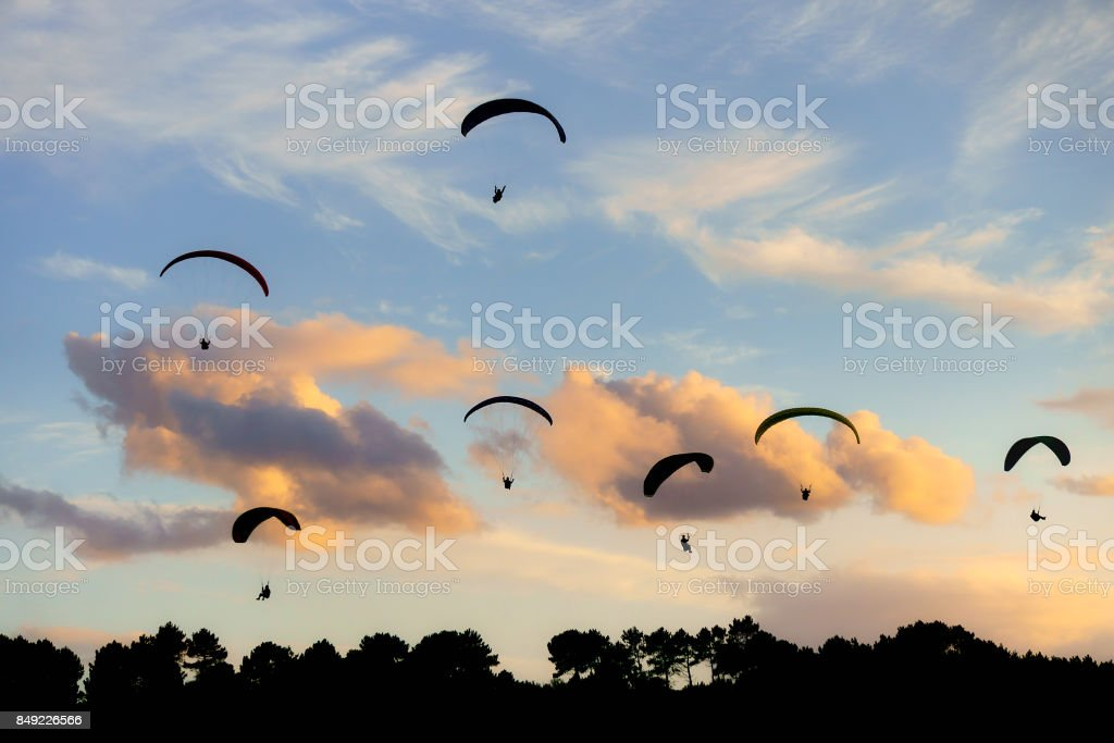 Group of Paraglides silhouettes stock photo