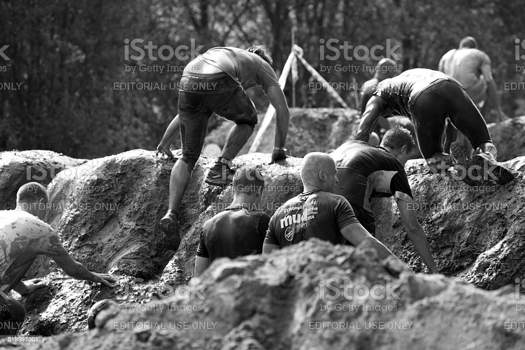 Group of participants climbing over an obstacle at mud run stock photo