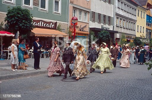 Bad Neustadt, Rhoen-Grabfeld, Bavaria, Germany, 1979. Historically citizens' festival. Group of participants in a town festival in clothes from the first half of the 19th century. Also: spectators, shops and buildings.