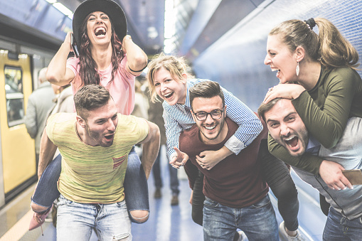 istock Group of party friends having fun in underground metropolitan station - Young people ready for night out  - Friendship and party concept - Warm desaturated filter - Focus on center man face glasses 864439968