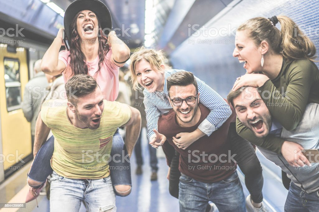Group of party friends having fun in underground metropolitan station - Young people ready for night out  - Friendship and party concept - Warm desaturated filter - Focus on center man face glasses stock photo