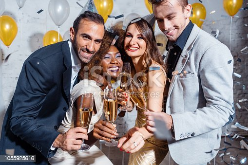 istock Group of party people celebrating with drinks 1055925616