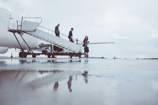 Group of passengers disembarking the airplane stock photo