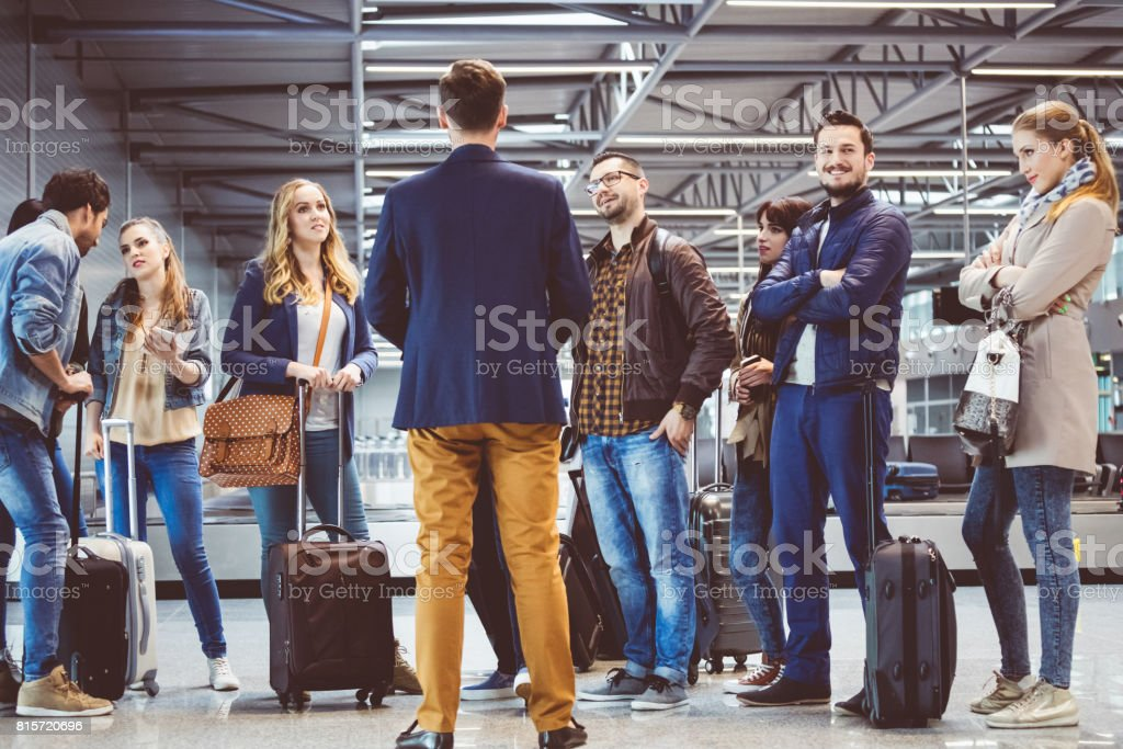 Group of passengers standing at airport lounge stock photo