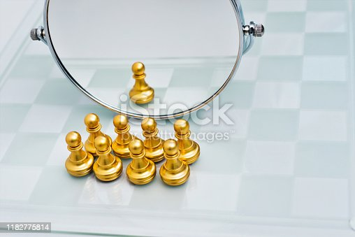 istock A group of pawns are in front of the mirror 1182775814